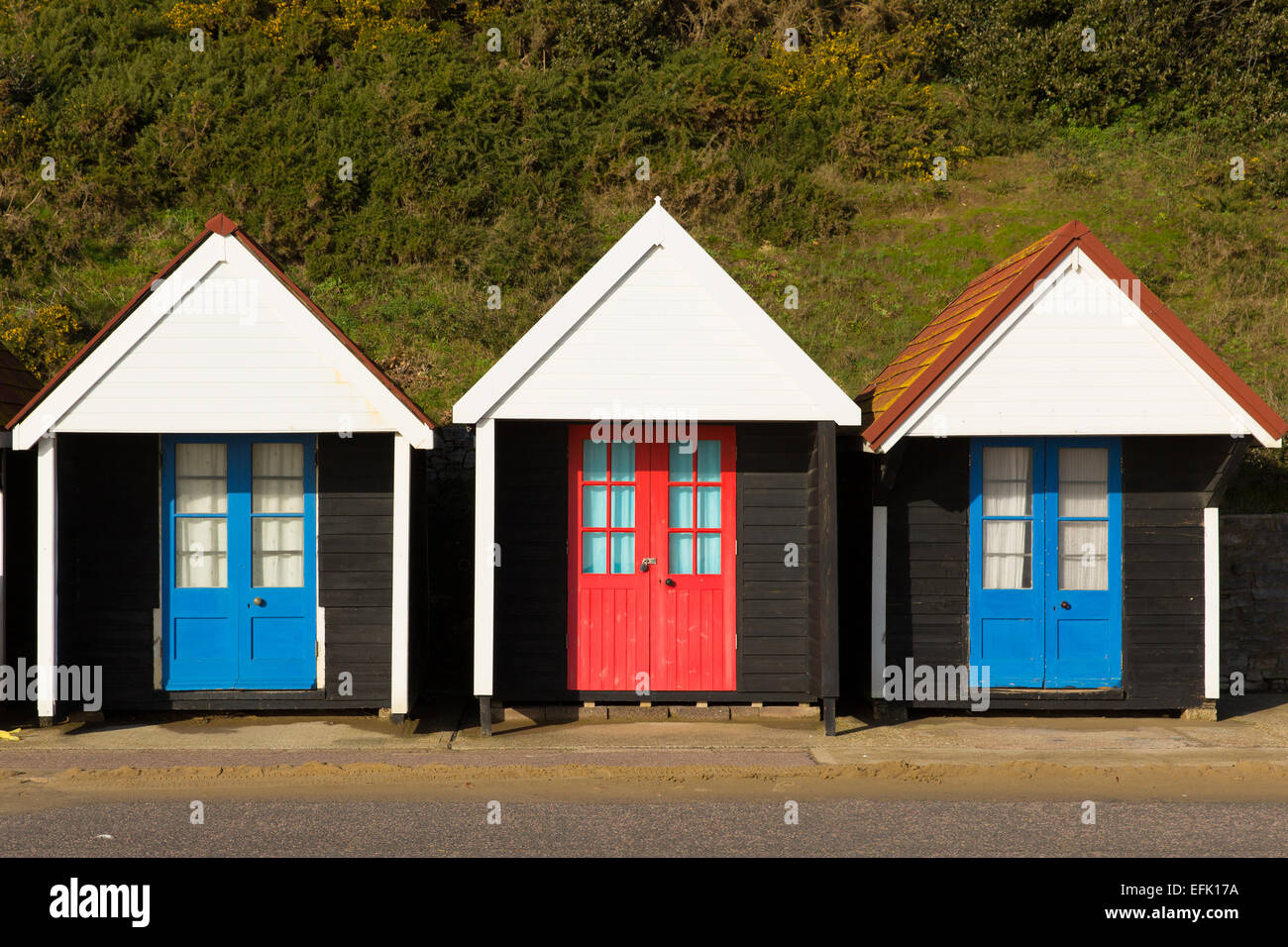 Three Colourful Beach Huts With Blue And Red Doors In A Row Stock