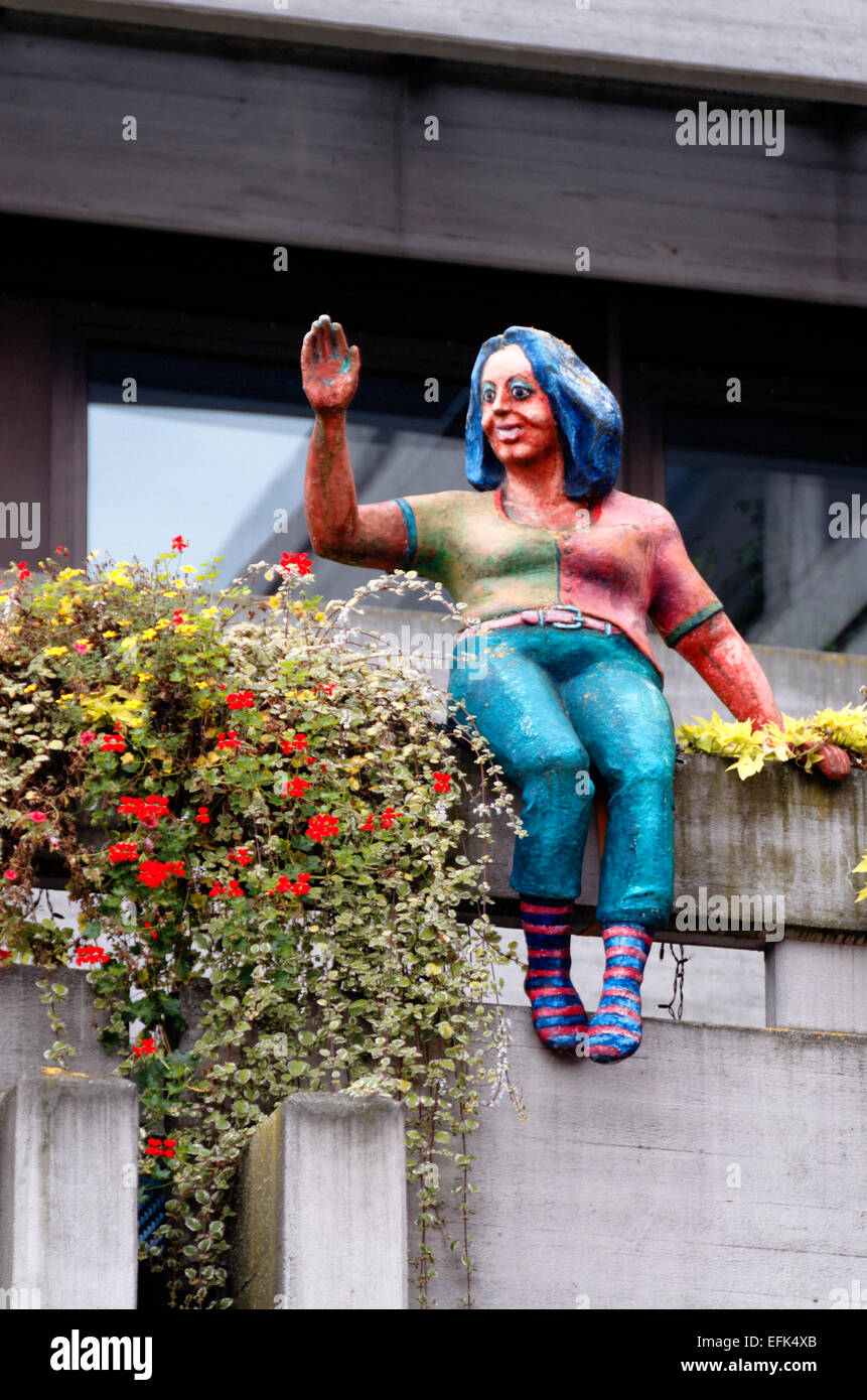 Statue of a waving Afro-Caribbean woman sitting on the ledge of offices in Arlen, Germany - Stock Image