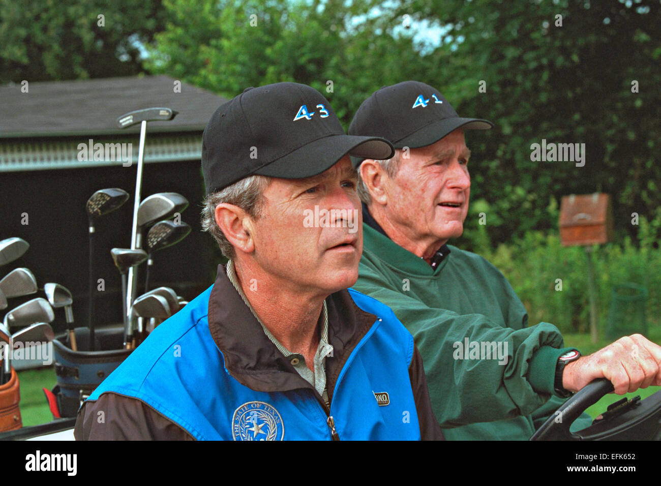 US President George W. Bush sits in a golf cart with his father former President George H.W. Bush wearing caps with - Stock Image
