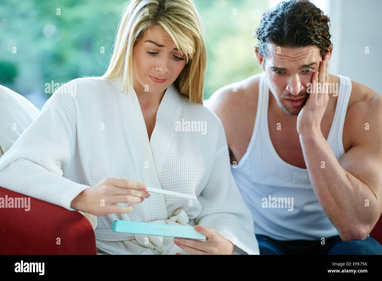 Unhappy couple finding out she is pregnant Stock Photo