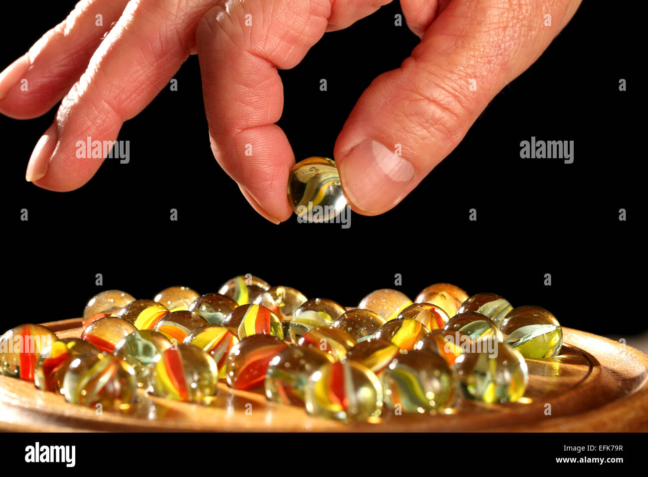 A man holds a marble in his hand while playing a game known as Solitaire in the United Kingdom. - Stock Image