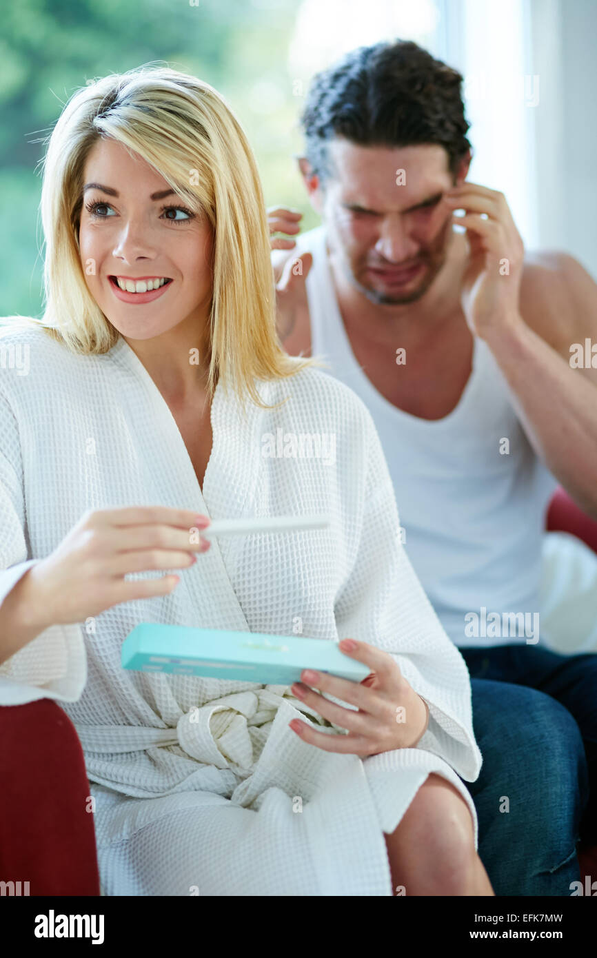 Happy girl finding out she is pregnant with upset man in background - Stock Image
