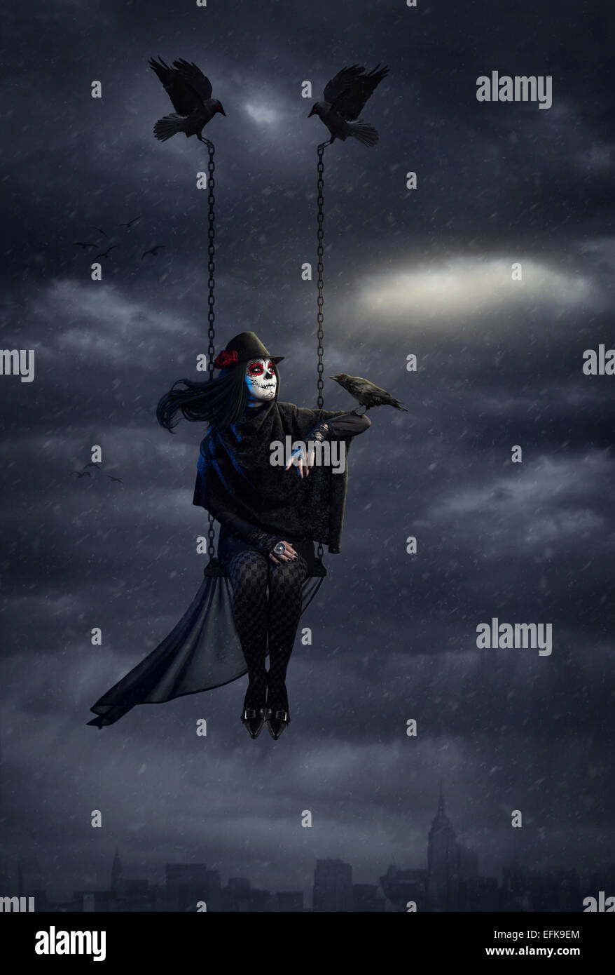 Woman with sugar skull makeup holding black crow and flying above the city at dark overcast sky with snowfall - Stock Image