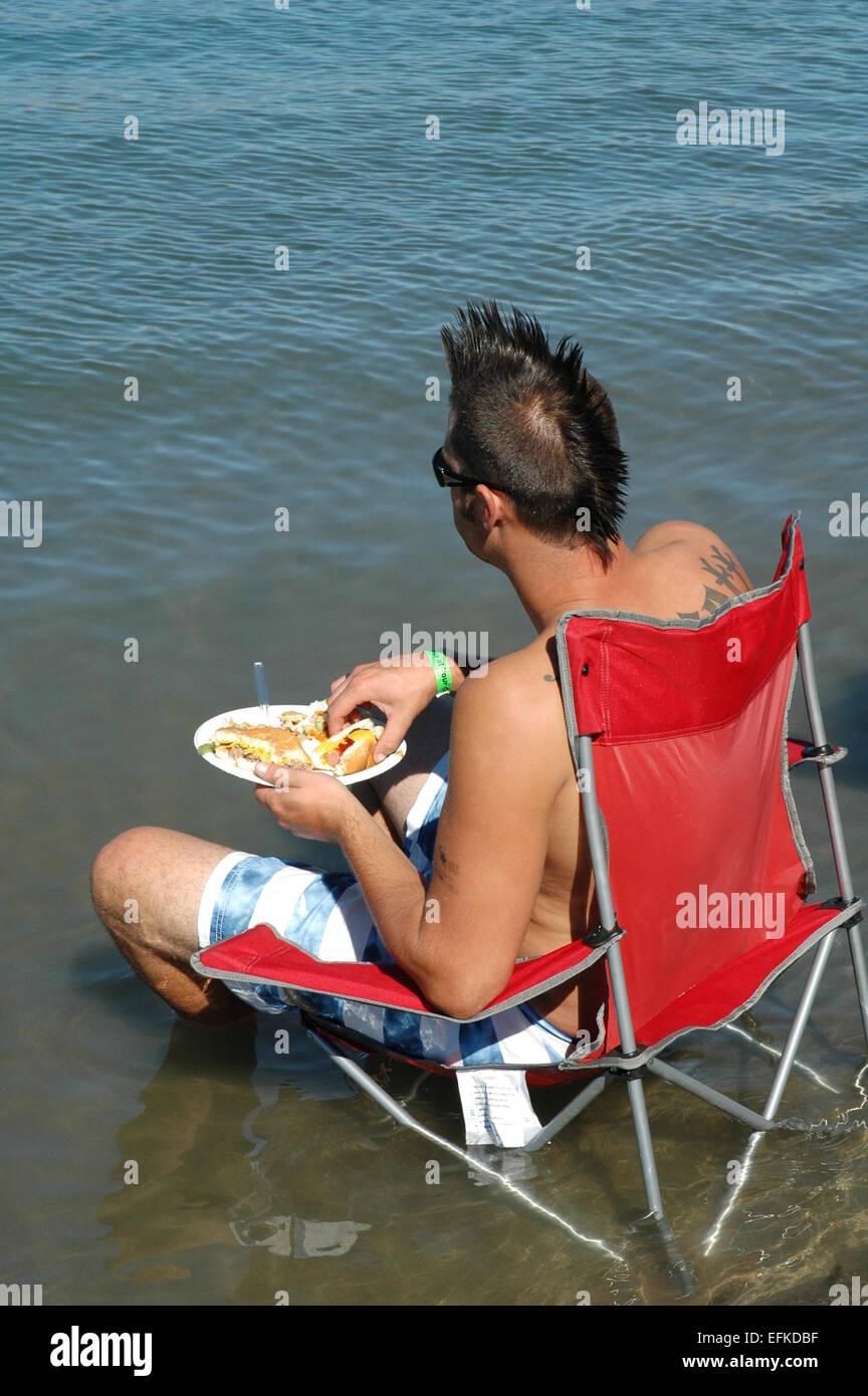 Man eating lunch at lake. - Stock Image