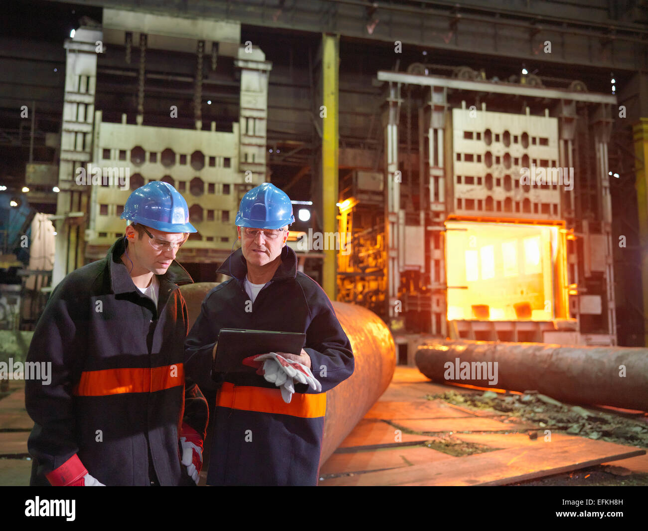 Steelworkers with digital tablet in front of furnace in steelworks Stock Photo