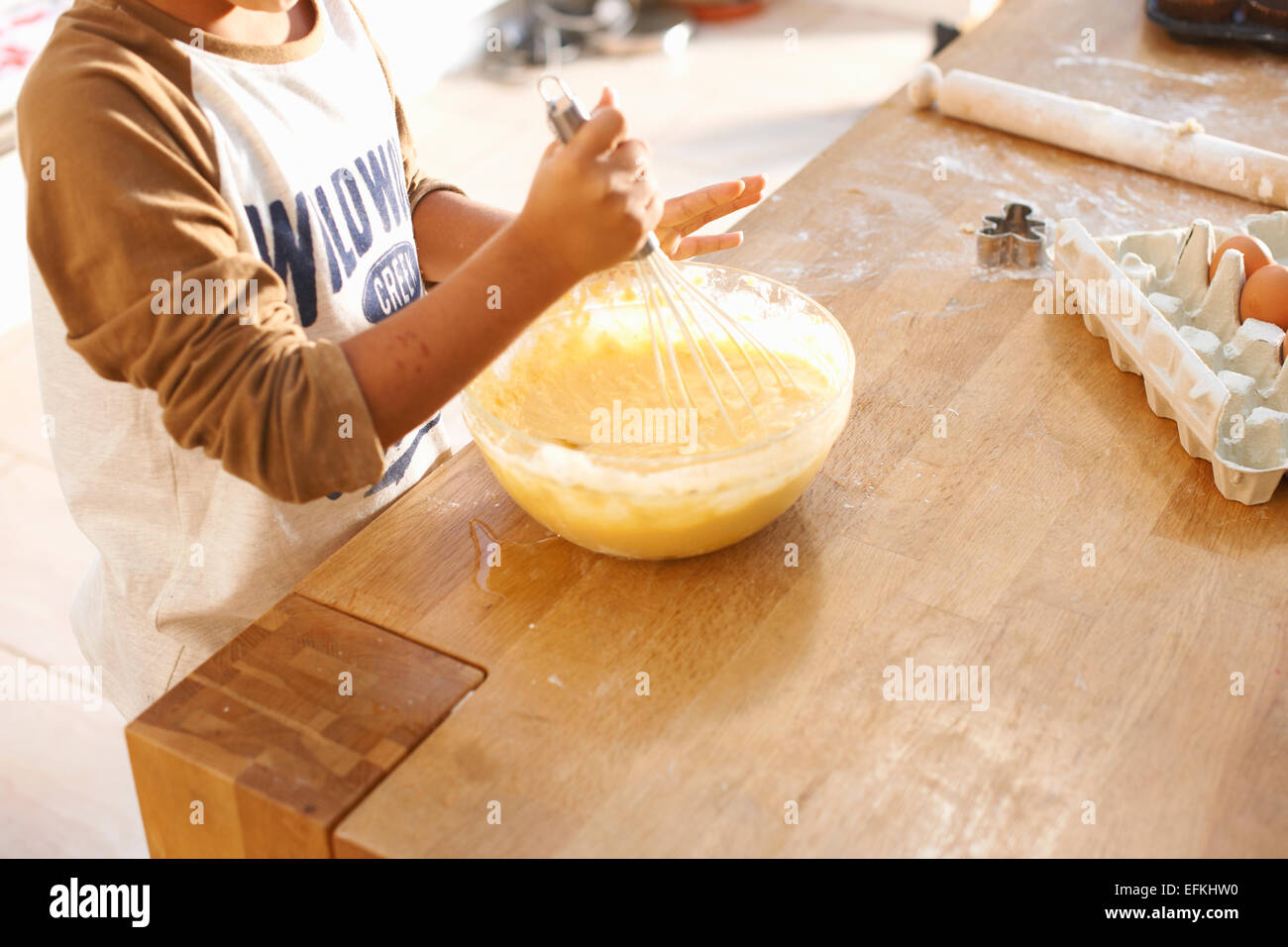 Boy beating mixture in bowl in kitchen - Stock Image