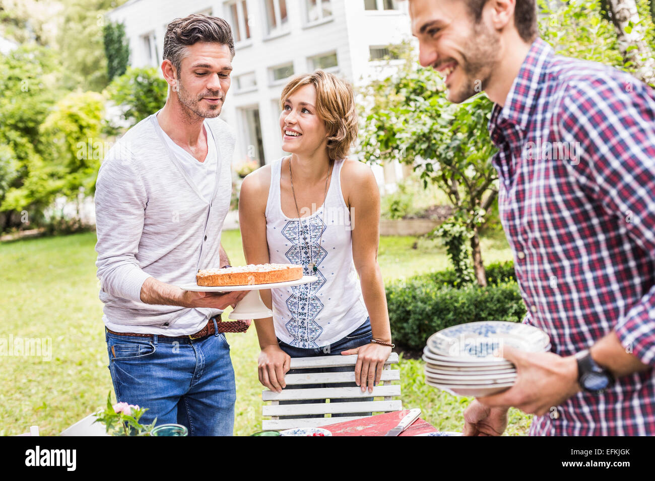 Group of friends setting up garden party, mid adult man carrying cake - Stock Image