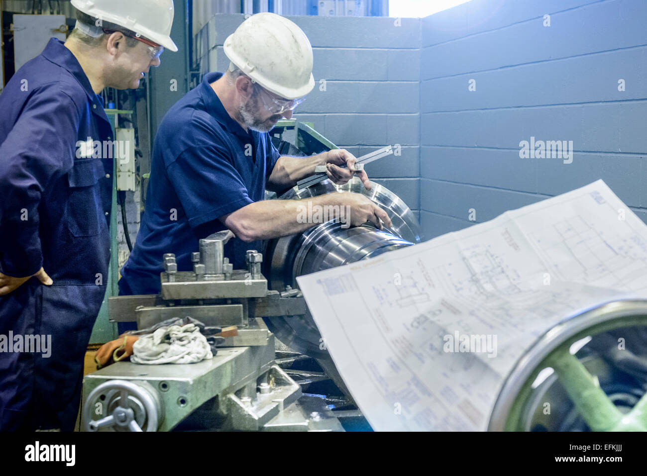 Engineers working on lathe with drawings - Stock Image
