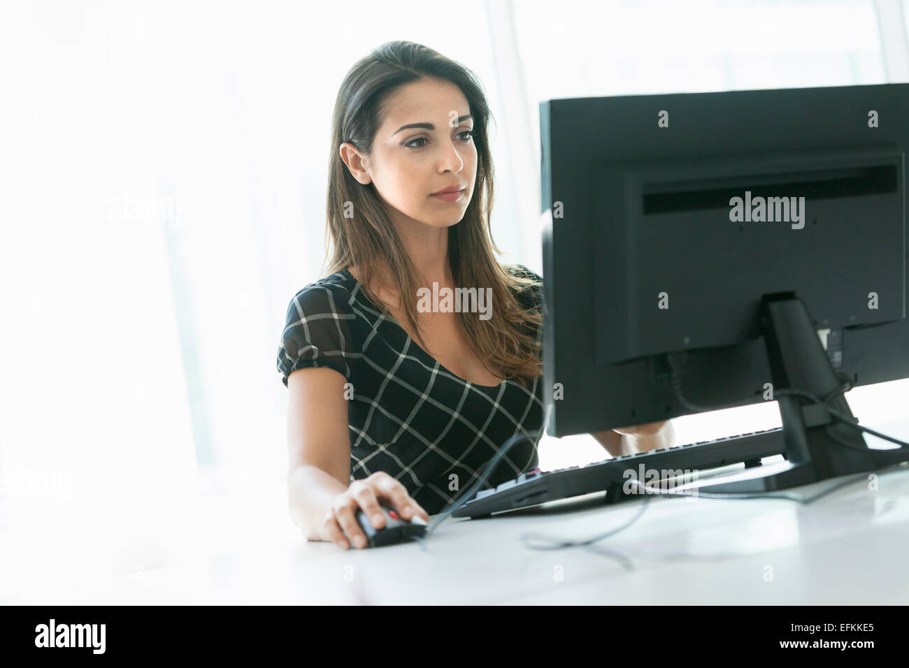 Woman using computer - Stock Image