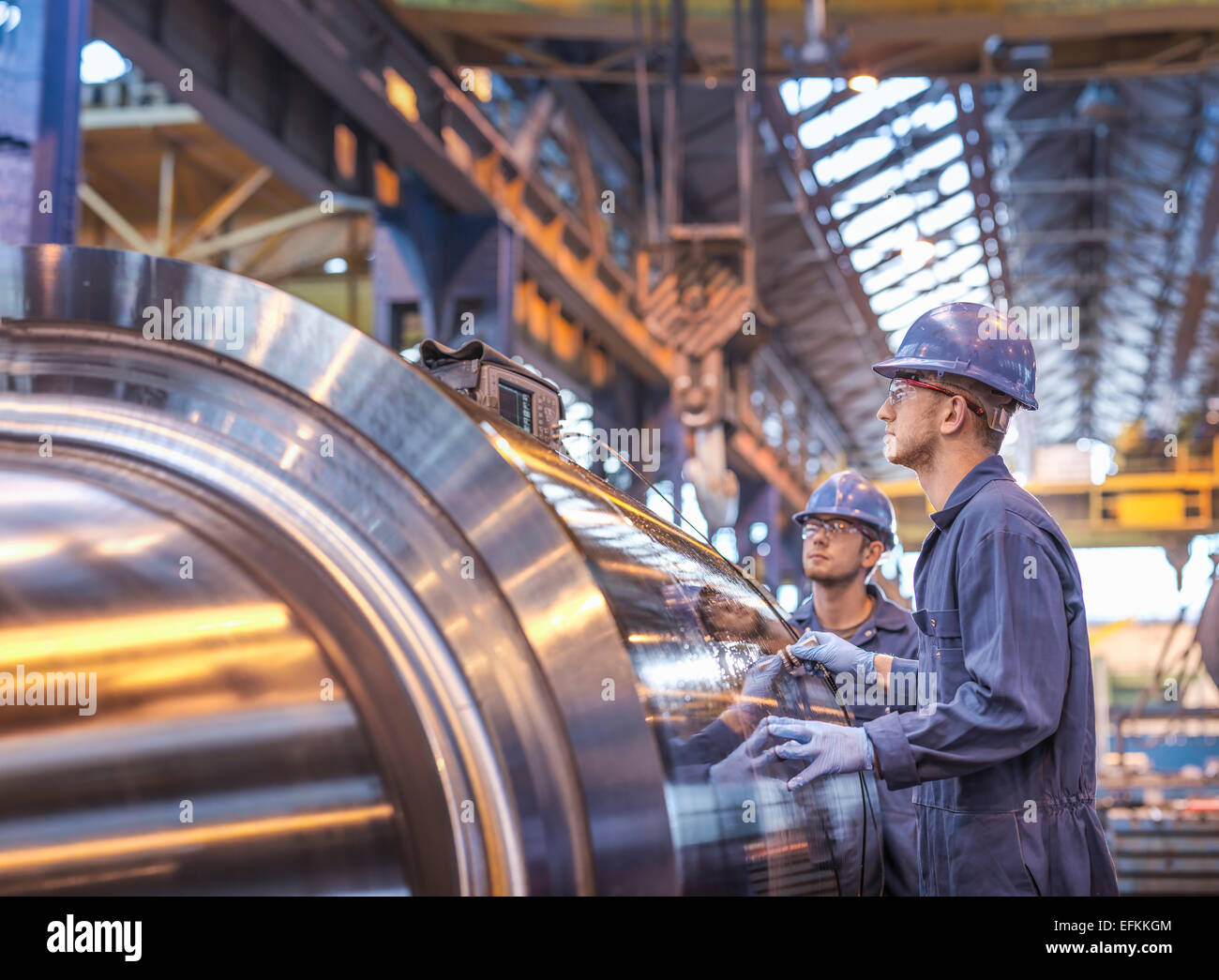 Engineers using ultrasound to check steel part in engineering factory - Stock Image