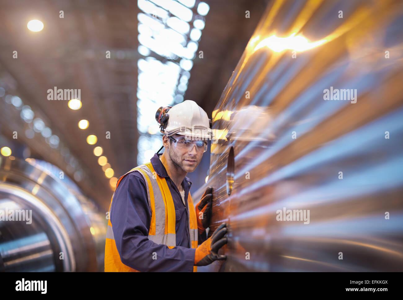 Engineer checking steel part in engineering factory - Stock Image