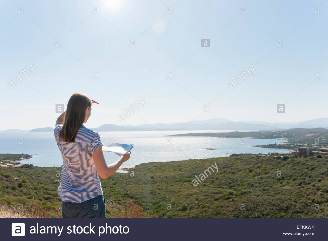 Rear view of mid adult woman holding map and looking at coastal view, Sardinia, Italy - Stock Image