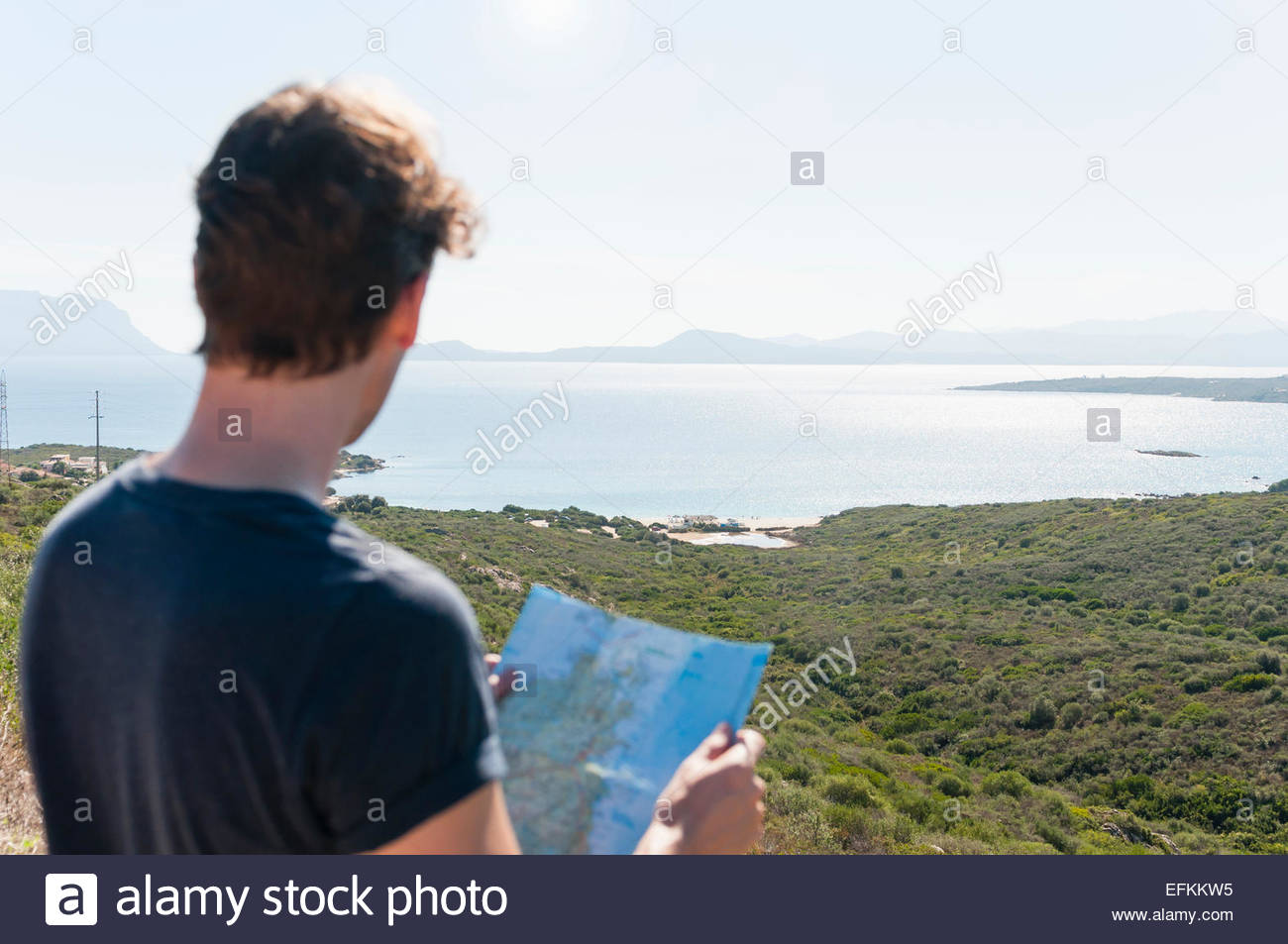 Rear view of mid adult man holding map and looking at coastal view, Sardinia, Italy - Stock Image