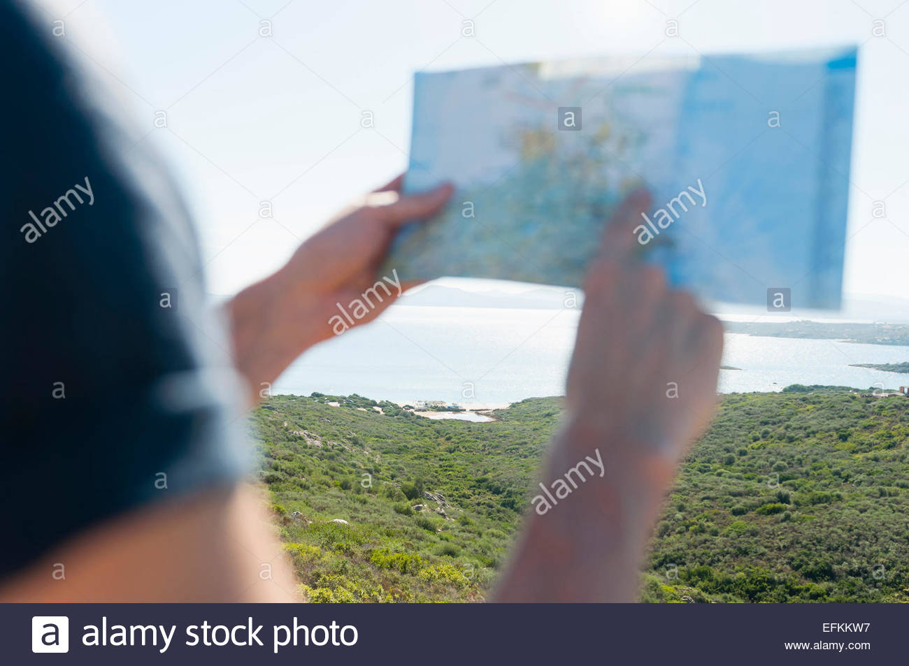 Cropped view of mans hands holding map at coast, Sardinia, Italy - Stock Image