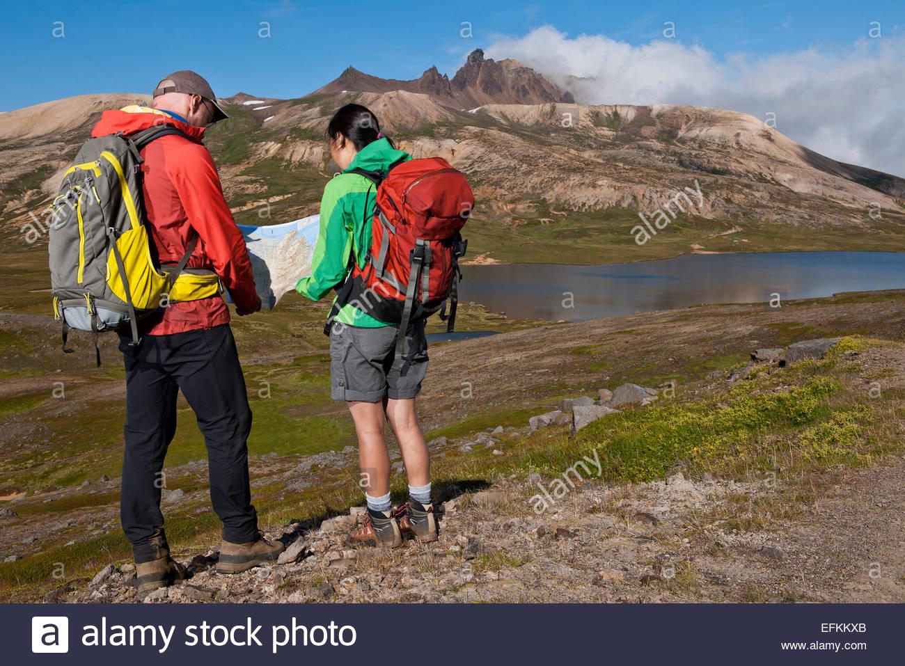 Mature hiking couple checking direction on map, Breidvik, Borgafjordur East, East Iceland - Stock Image