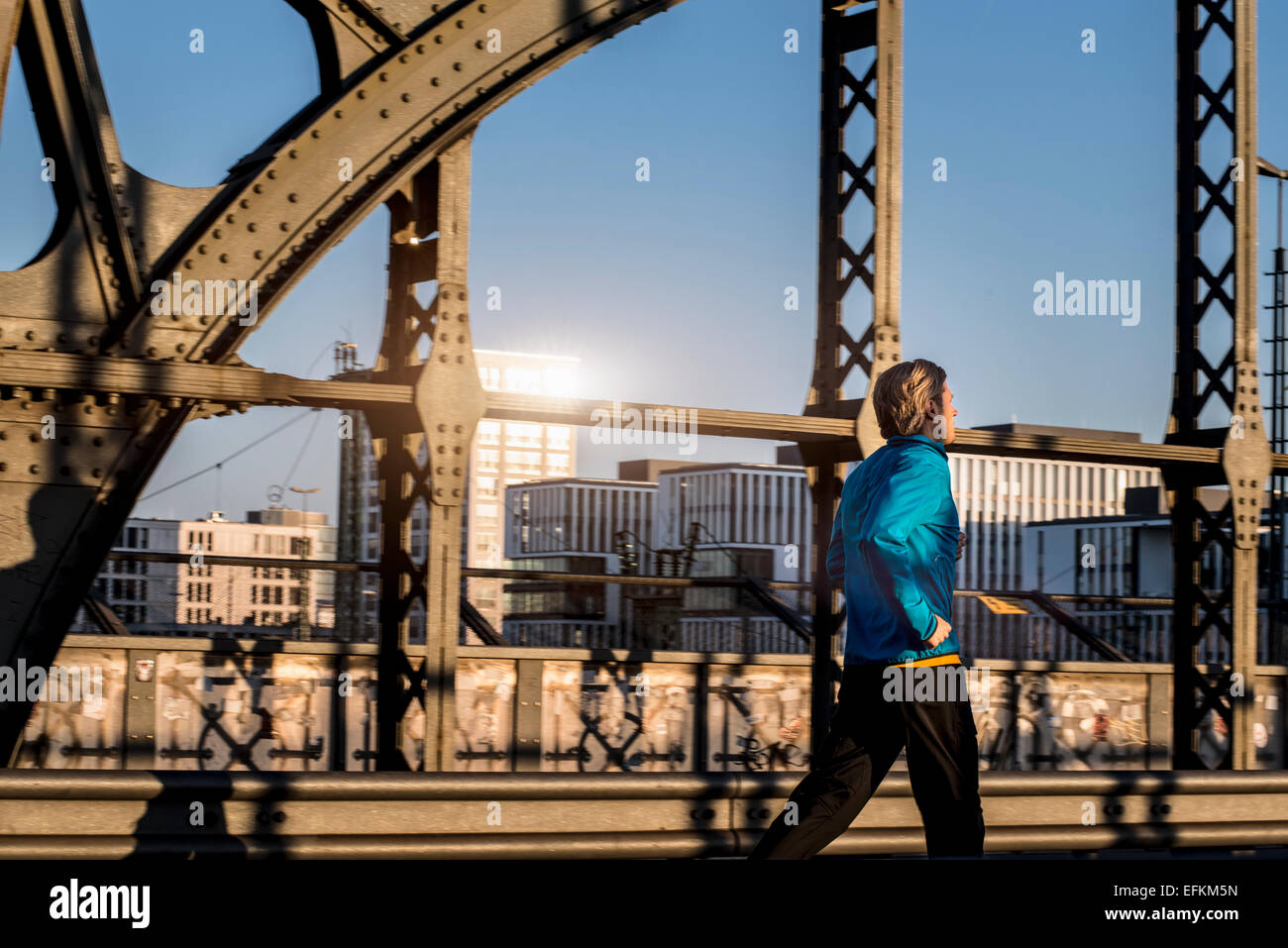 Man jogging on bridge, Munich, Bavaria, Germany - Stock Image