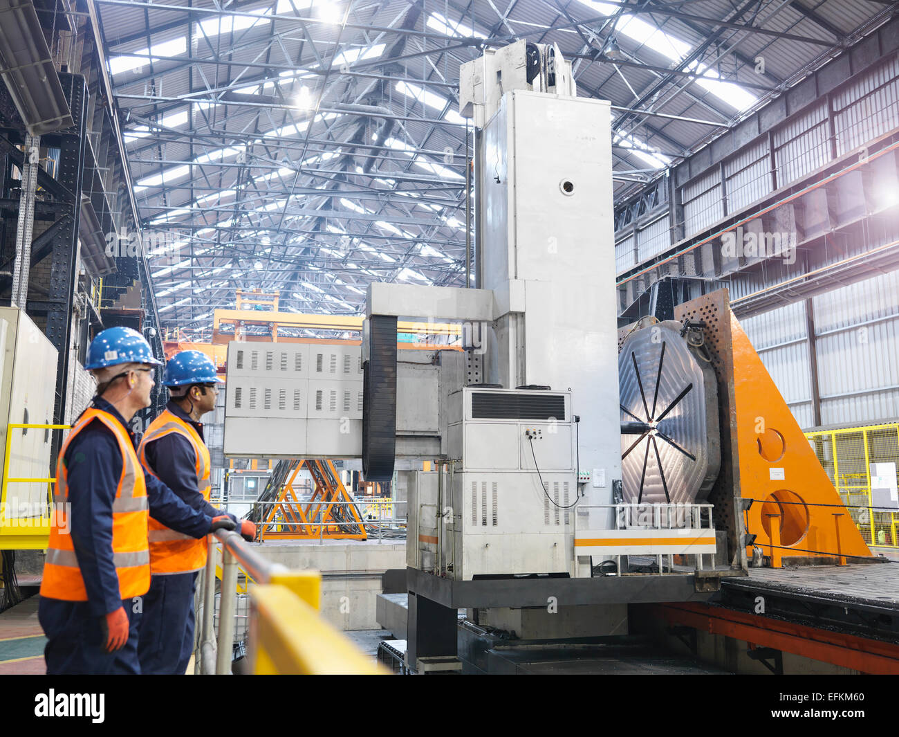 Steelworkers with gantry milling machine in engineering factory - Stock Image
