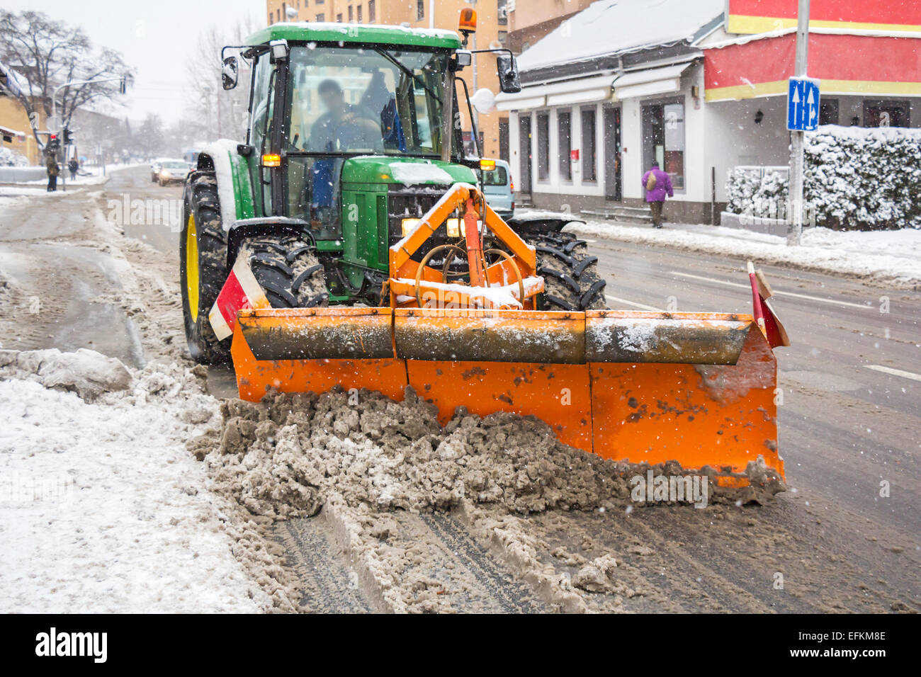 Snowplow tractor removing snow from city road - Stock Image