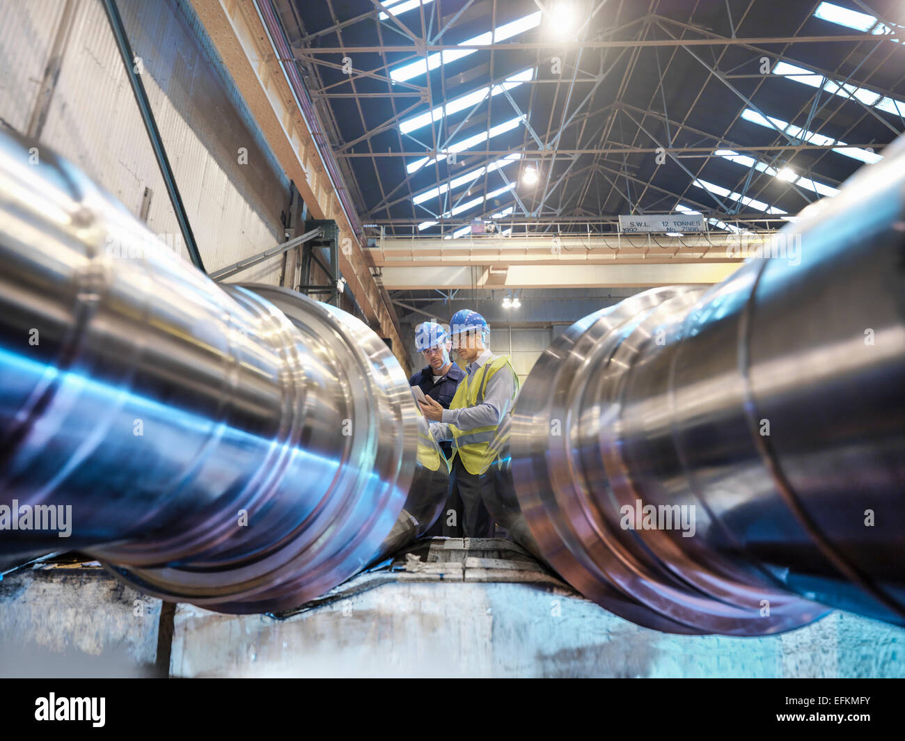 Engineers inspecting finished steel rollers in engineering factory, low angle view - Stock Image