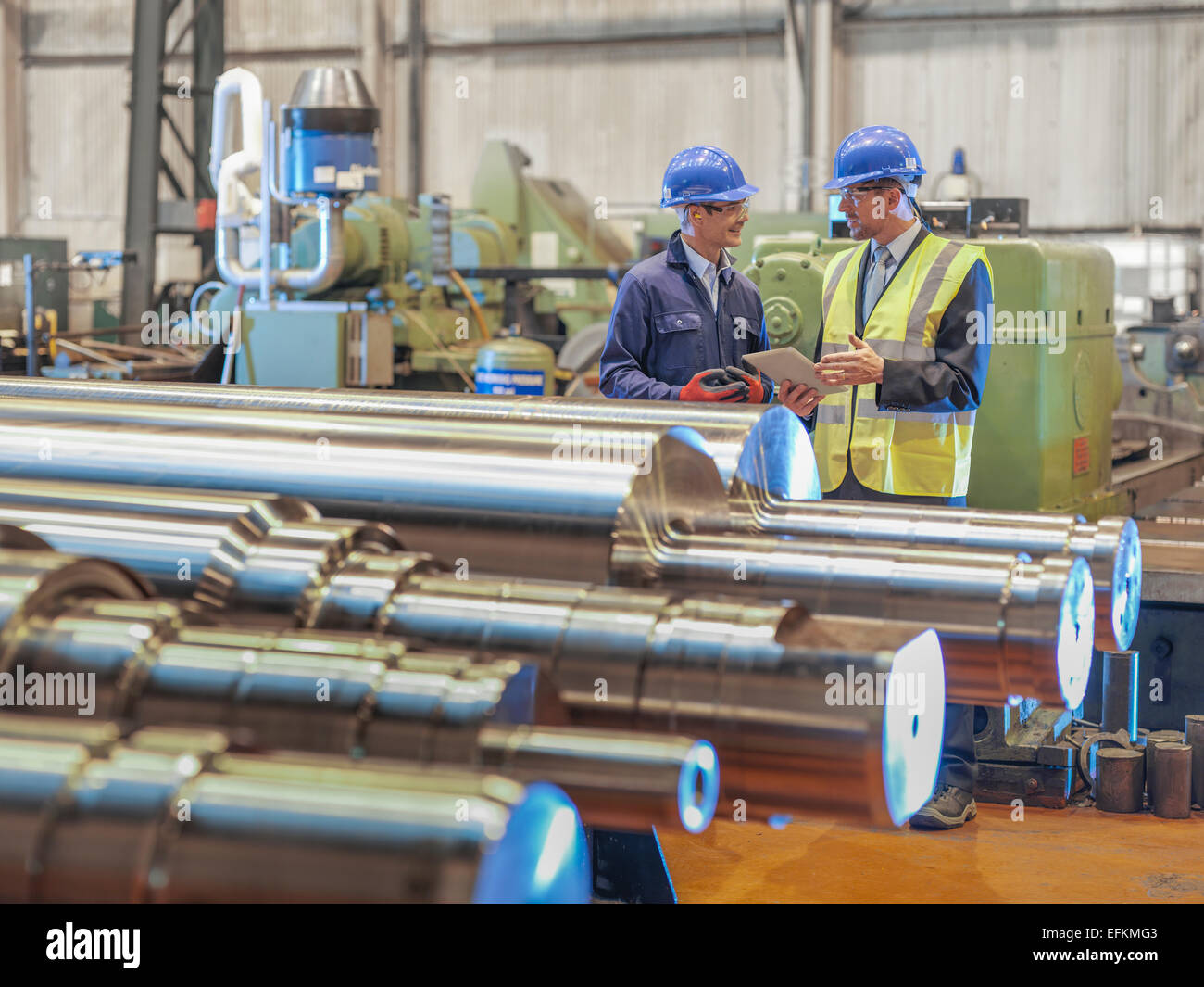 Engineers inspecting finished steel rollers in engineering factory - Stock Image