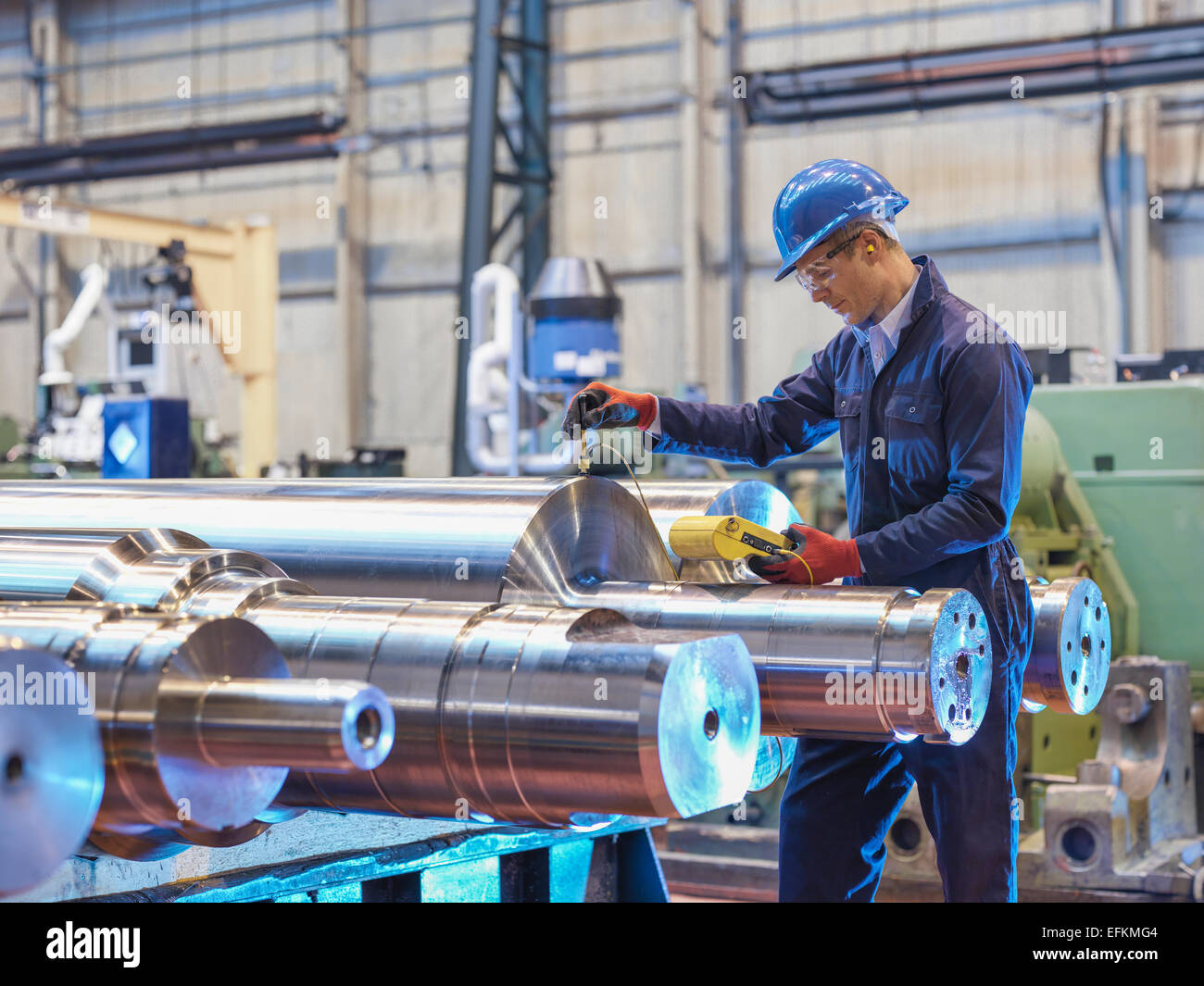 Engineer inspecting finished steel rollers in engineering factory - Stock Image
