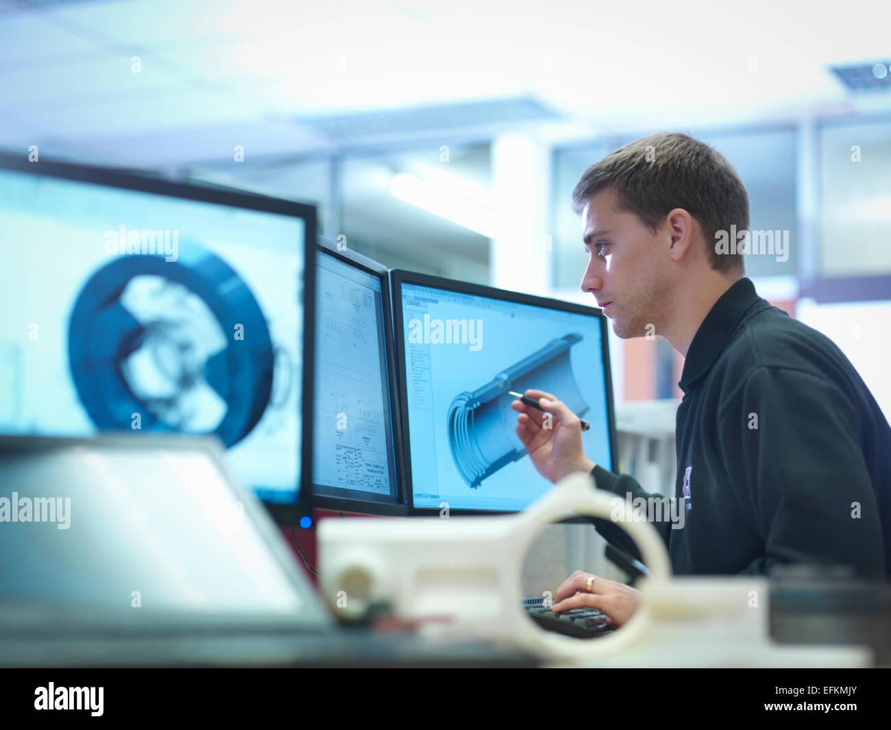 CAD designer working on engineering designs - Stock Image