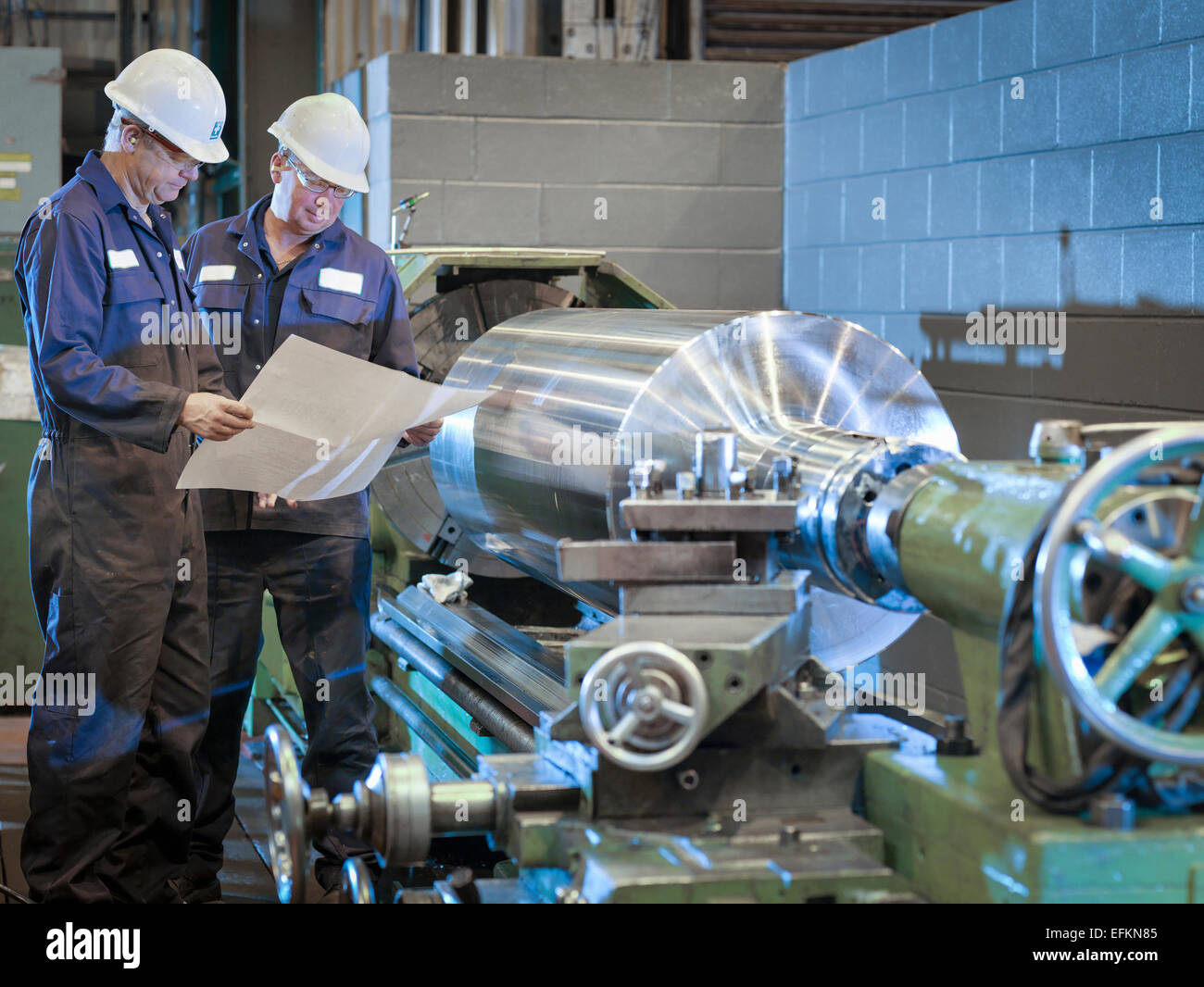 Engineers working with drawings on lathe - Stock Image