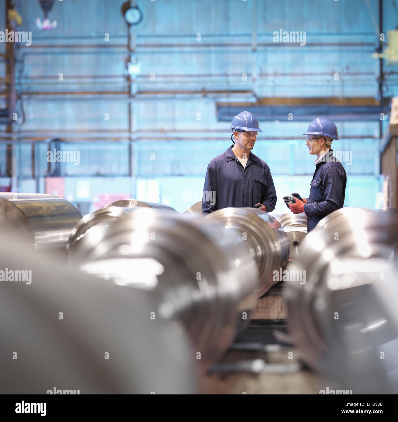 Engineers in discussion in engineering factory - Stock Image