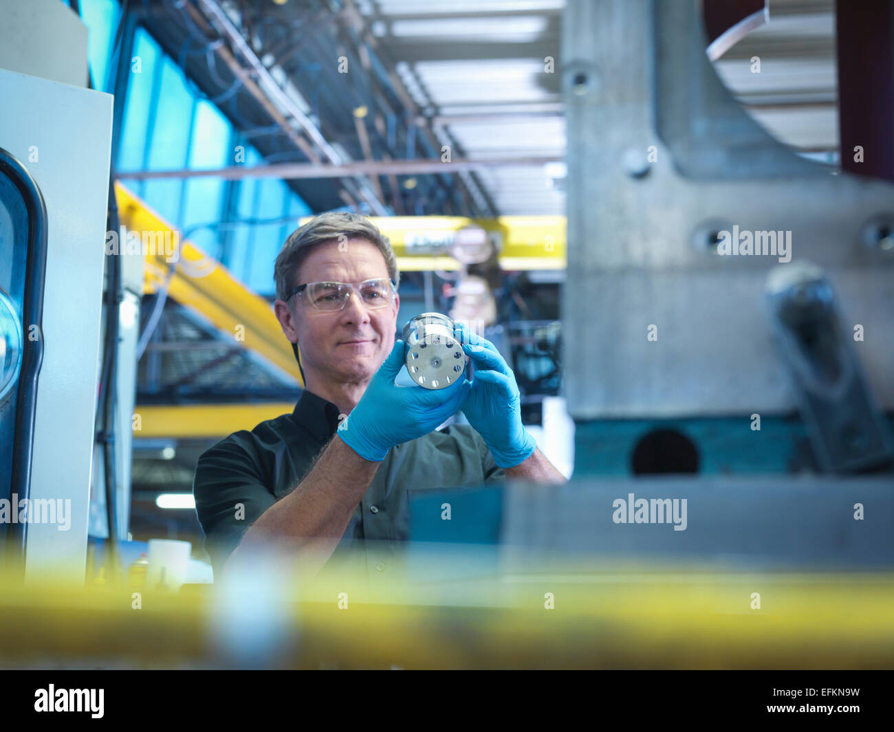Engineer inspecting part in factory - Stock Image