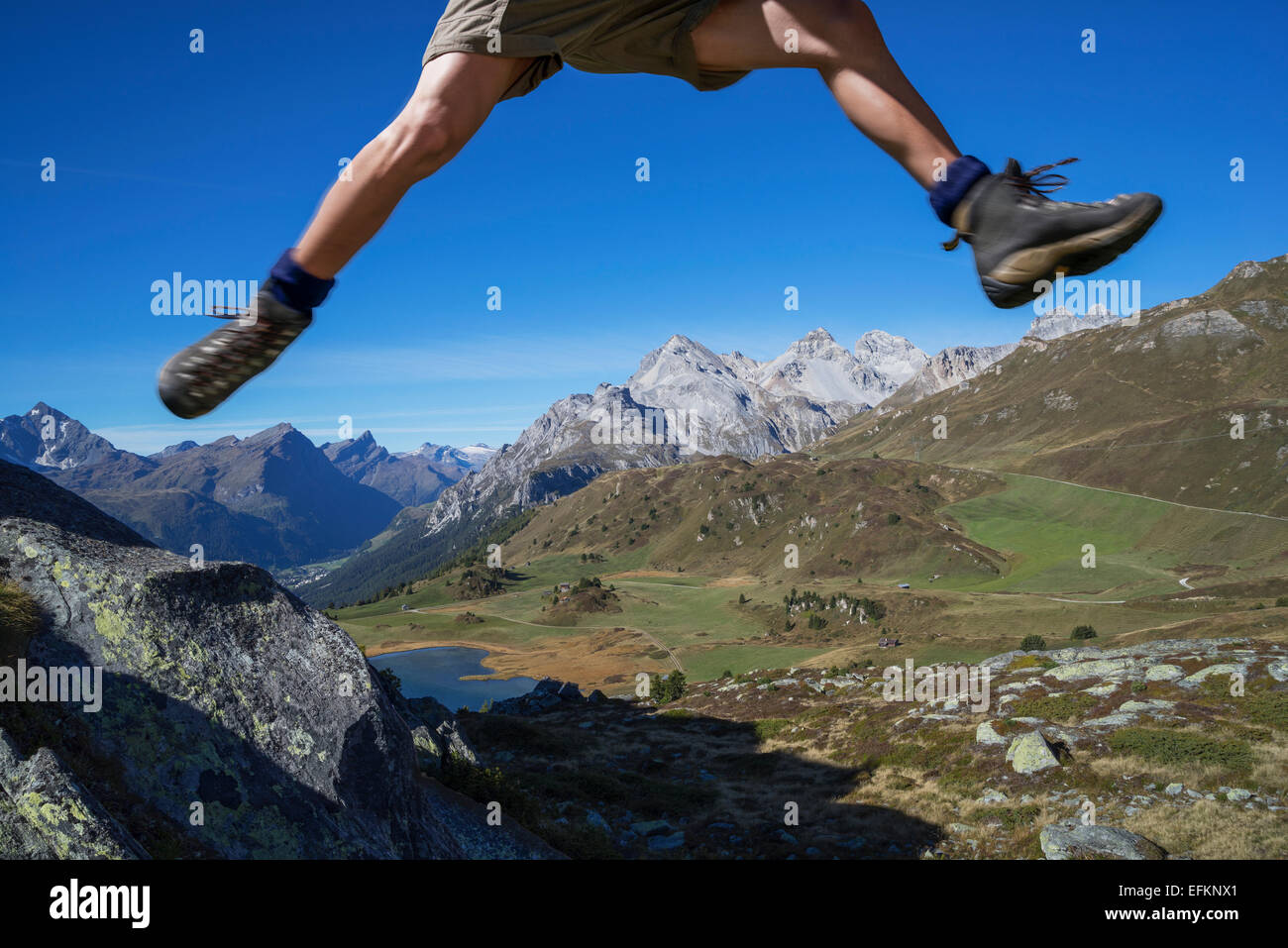 Legs of male hiker jumping over rocks, Lai da Fons, Canton Graubunden, Switzerland - Stock Image