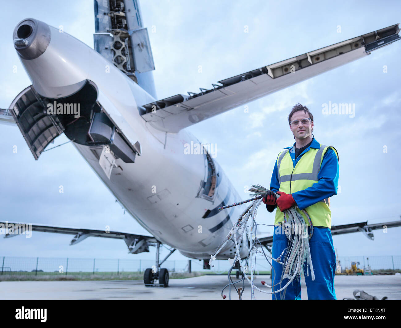 Engineer recycling aircraft parts on runway, portrait - Stock Image