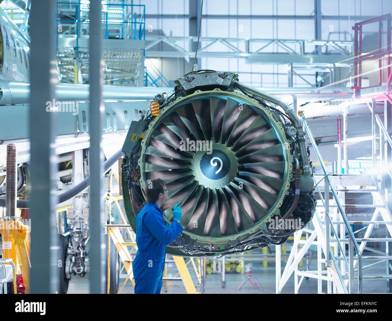Engineer inspecting jet engine in aircraft maintenance factory - Stock Image