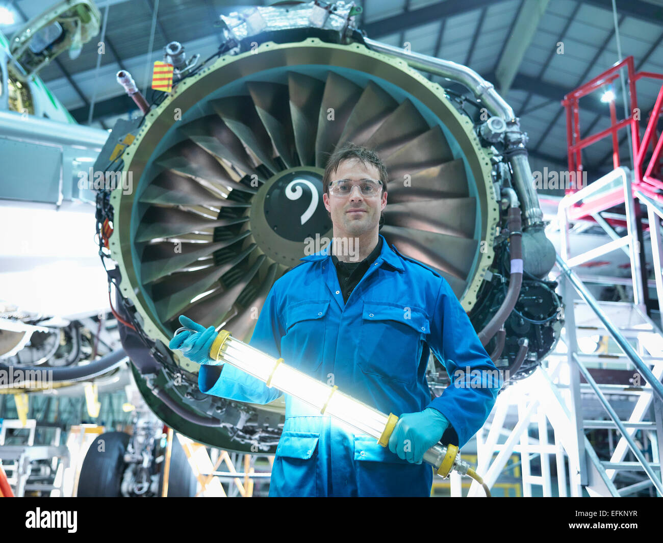 Portrait of engineer in front of jet engine in aircraft maintenance factory - Stock Image