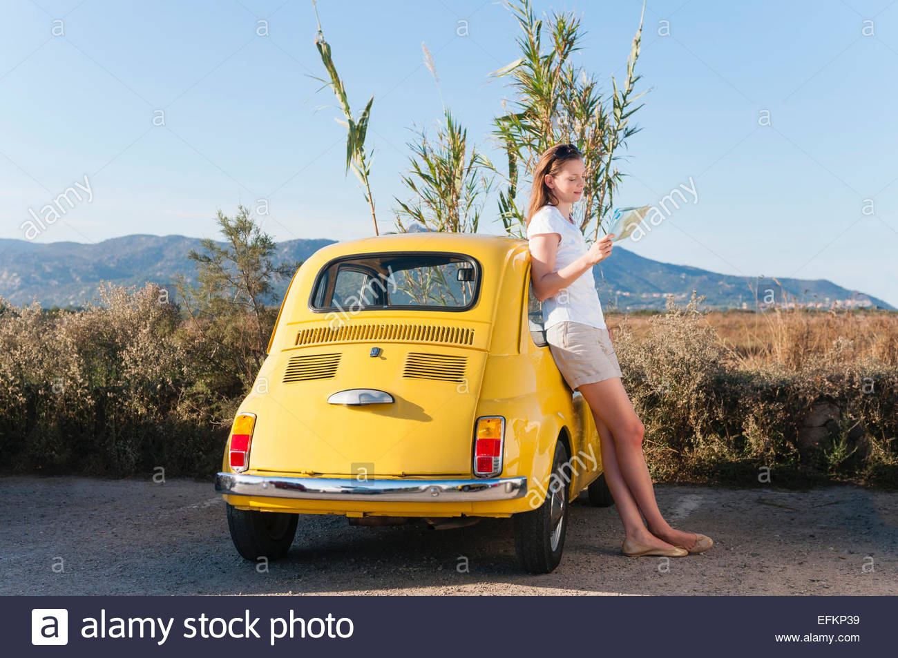 Mid adult woman reading map against yellow retro car, Sardinia, Italy - Stock Image
