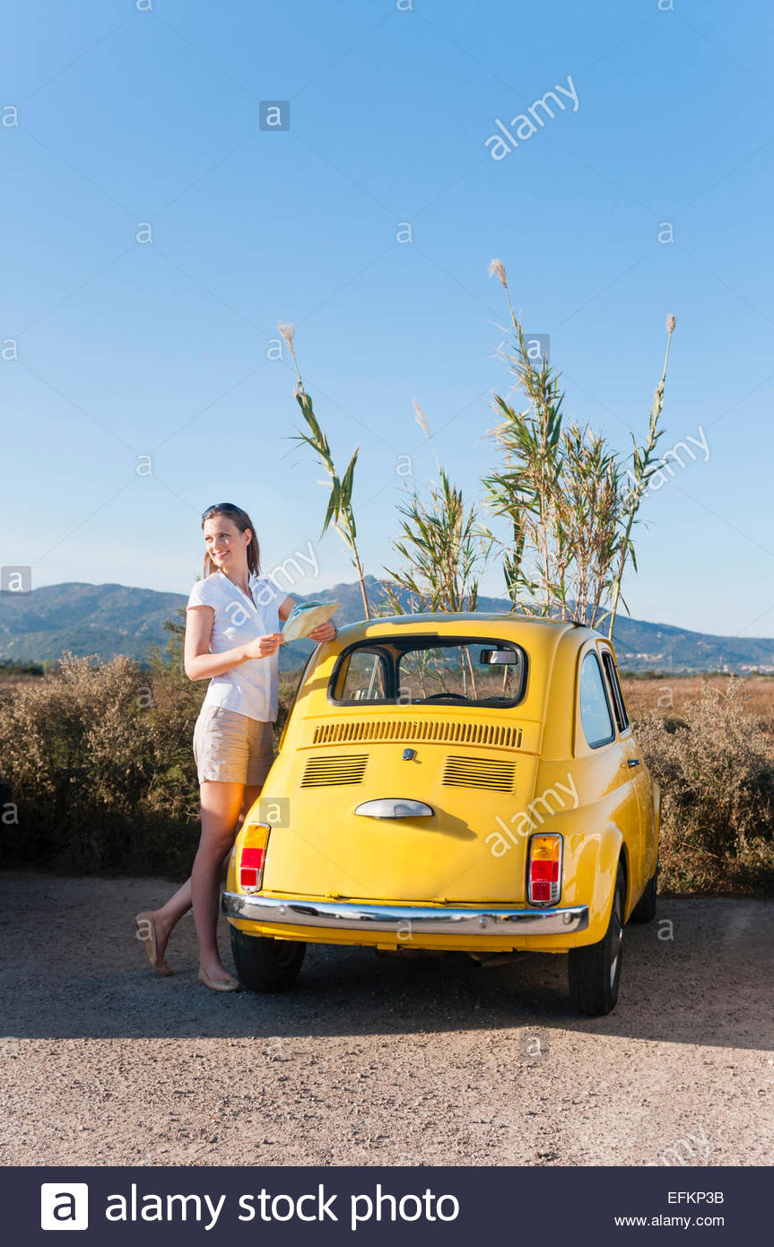 Mid adult woman with map and yellow retro car, Sardinia, Italy - Stock Image