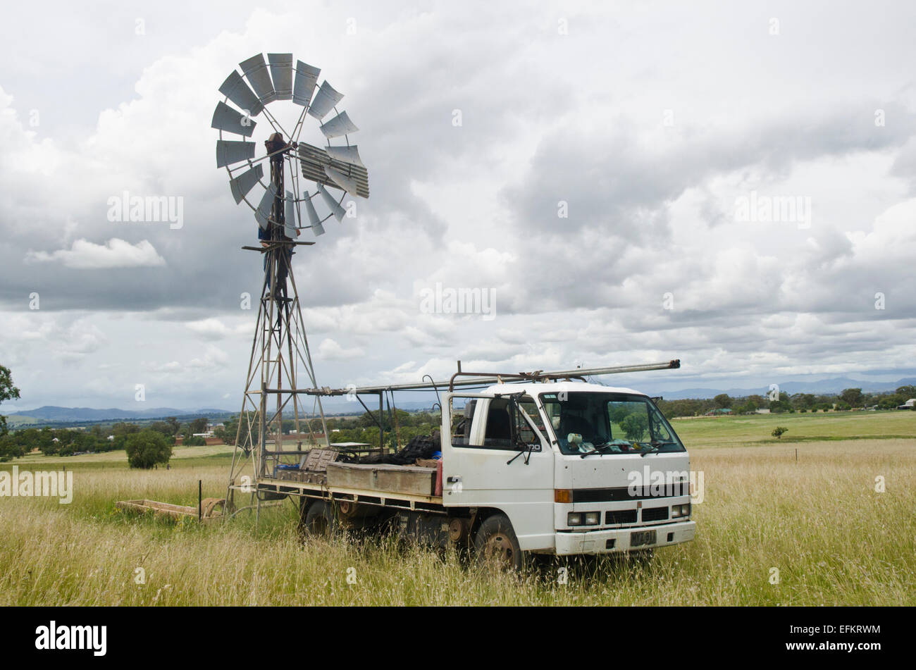 Repairman working on a rural windmill. - Stock Image