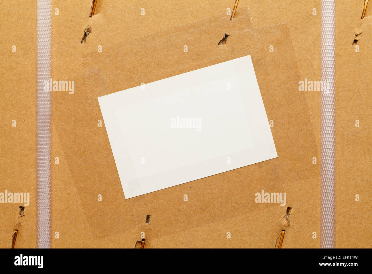 Cardboard Box with Large Staples, Plastic Straps and Blank Label. - Stock Image
