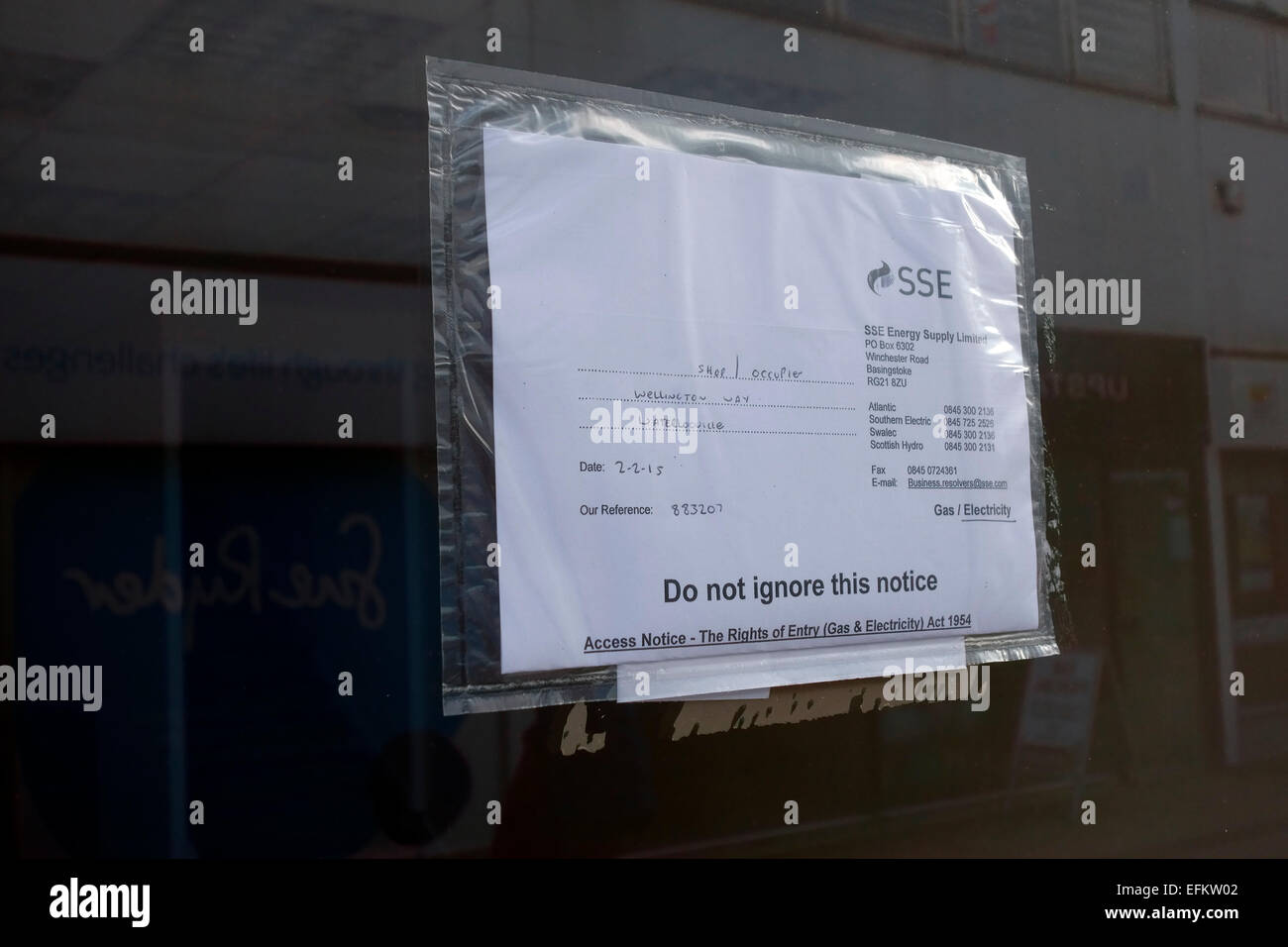Access notice taped to the front of an empty shop to read an electricity meter - Stock Image
