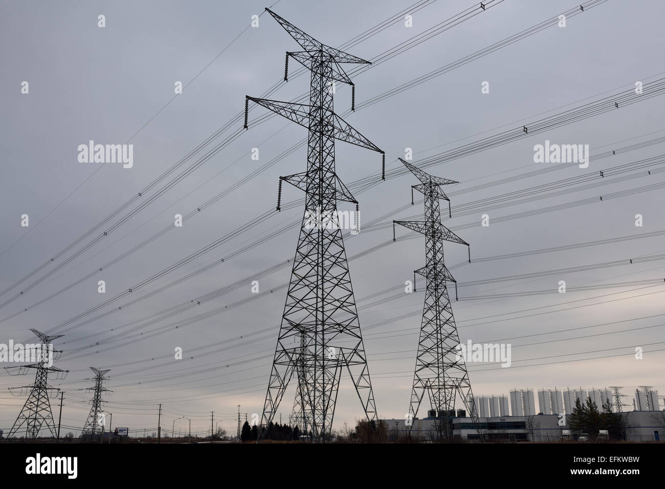 Hydro towers and high tension electricity power lines in an industrial park with cloudy sky Vaughan Canada - Stock Image