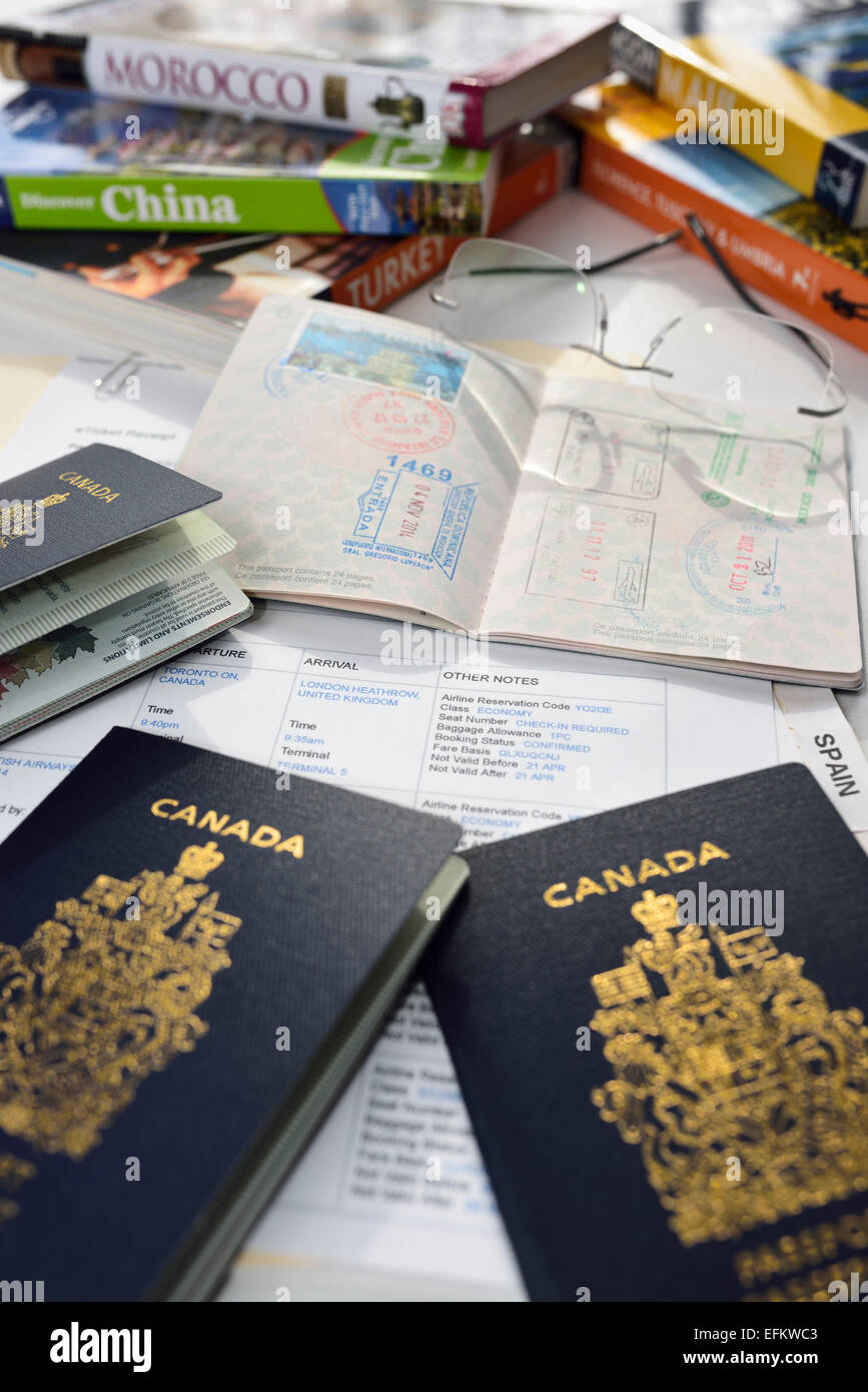 Preparation for International vacation travel with guide books, airfare itinerary, and Canadian passports - Stock Image