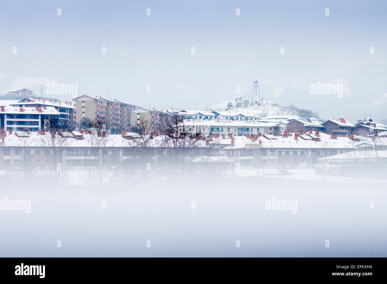 Panoramic view of Azkoitia village in winter with snow and San Martin clock on the top of the hill, Gipuzkoa, Basque - Stock Image