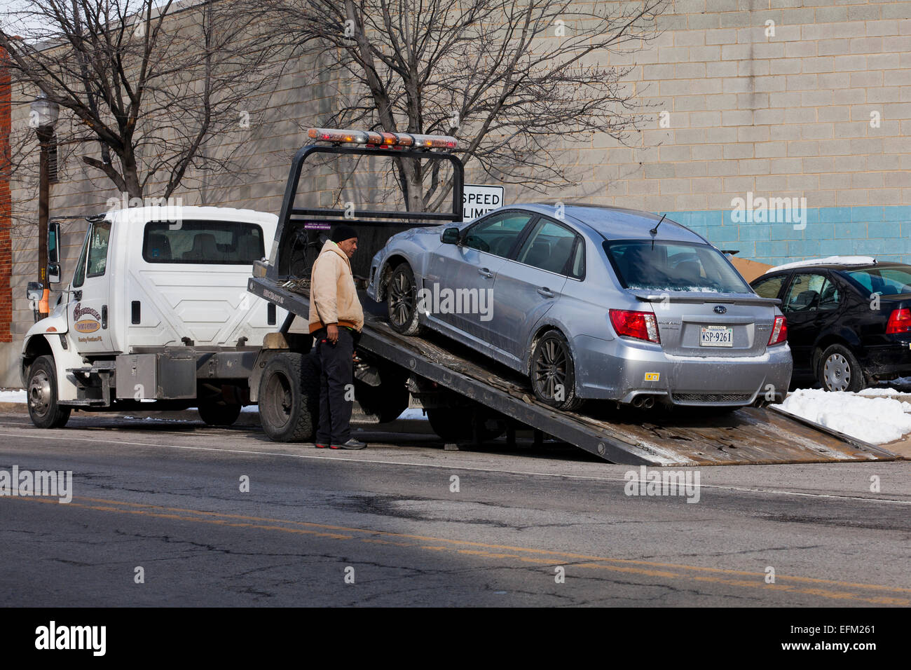 Tow truck driver loading car on flat bed - USA - Stock Image