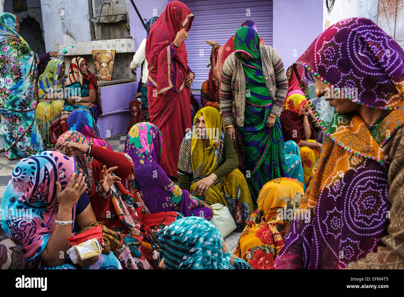 A group of colorfully dressed women mourning a death of a person in Pushkar, Rajasthan, India - Stock Image
