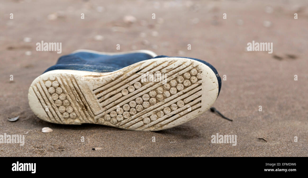 Still life: A gumboot, washed ashore, on the beach at Katwijk aan Zee, South Holland, The Netherlands. - Stock Image