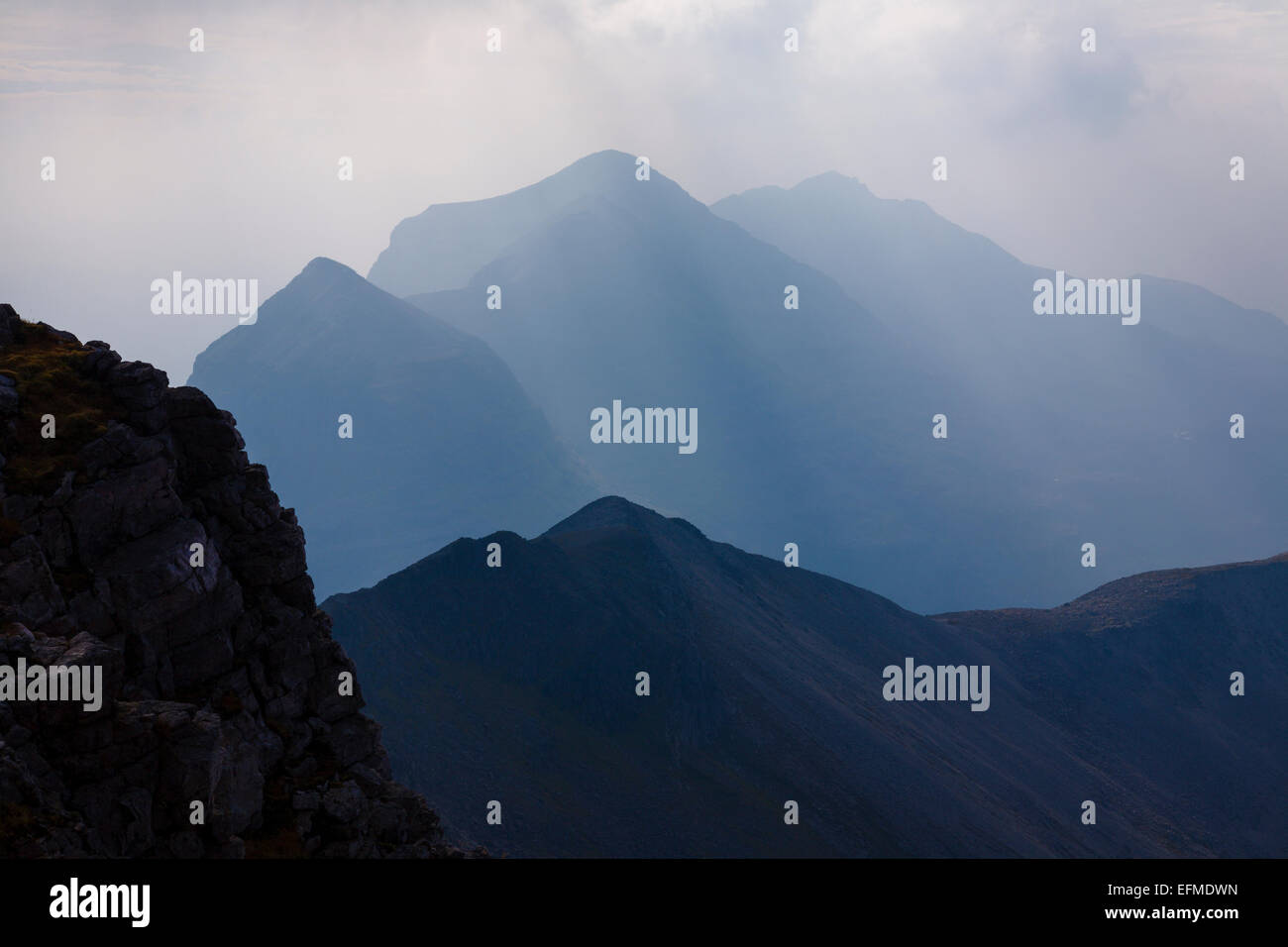 Liathach looming behind the impressive ridge of Beinn Eighe. - Stock Image