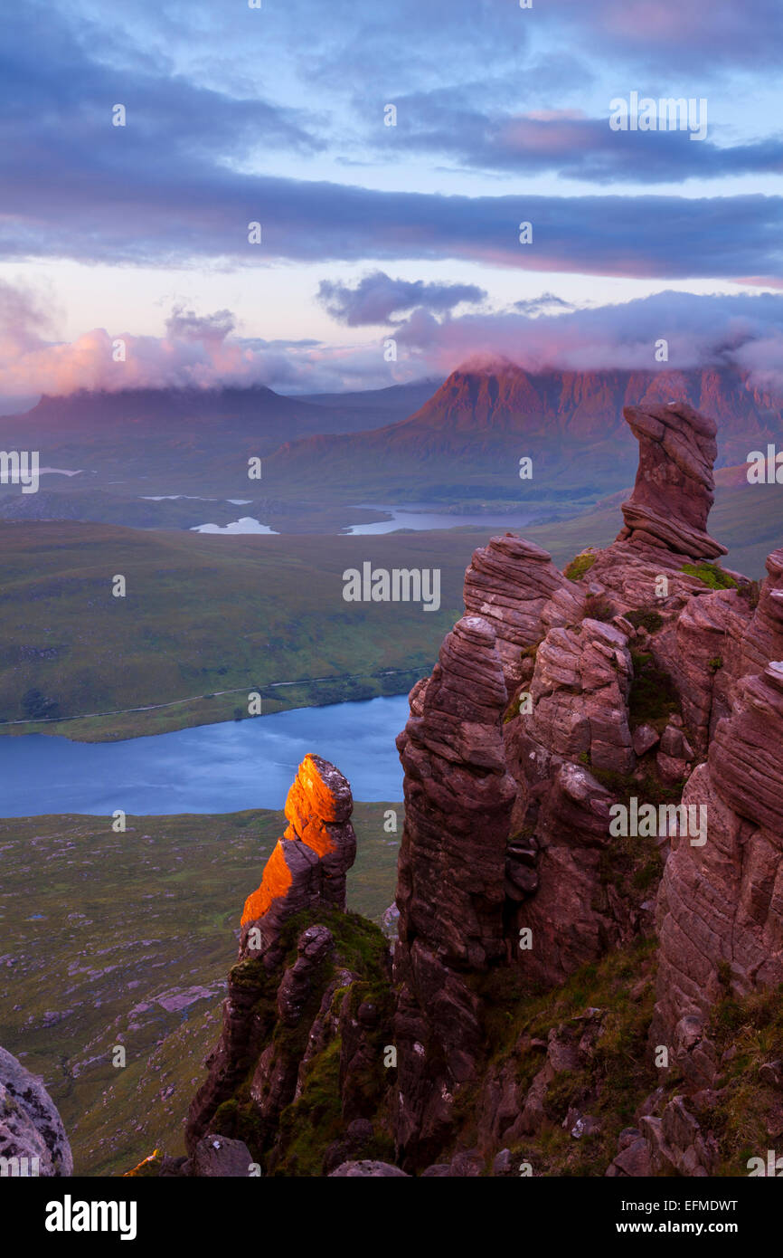 Beautiful Torridonian sandstone rock formations glowing in red evening light with Suilven and Cul Mor in Assynt - Stock Image
