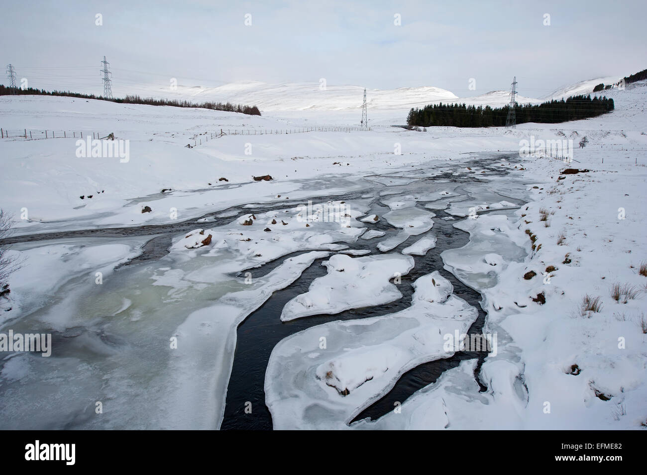 The River Spey in mid Winter frozen with only a trickle of water flow.  SCO 9542. - Stock Image
