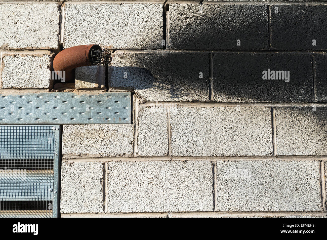 Metal exhaust pipe coming from a block built building with soot stains. - Stock Image