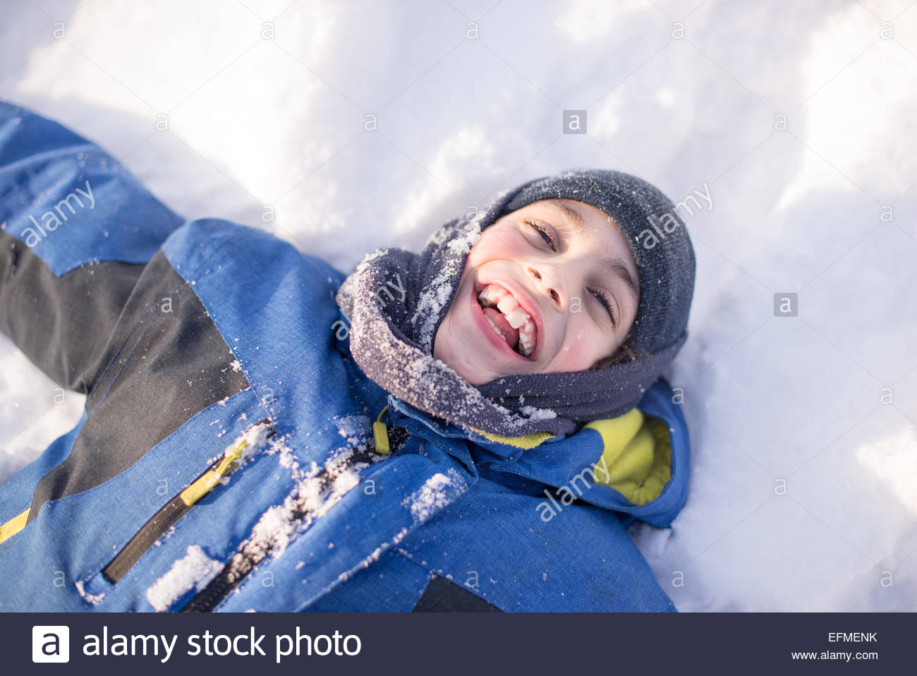 Hispanic child boy playing in the fresh white snow of the Canadian Winter - Stock Image