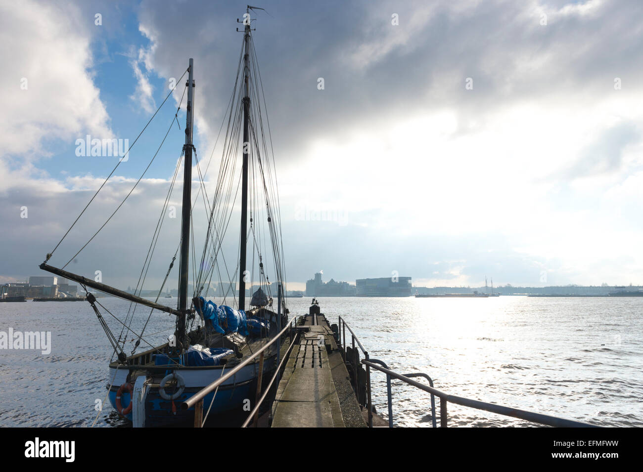 Winter light floods the Ij seen from a wharf in Amsterdam North, with an old Dutch sailing barge in the foreground - Stock Image